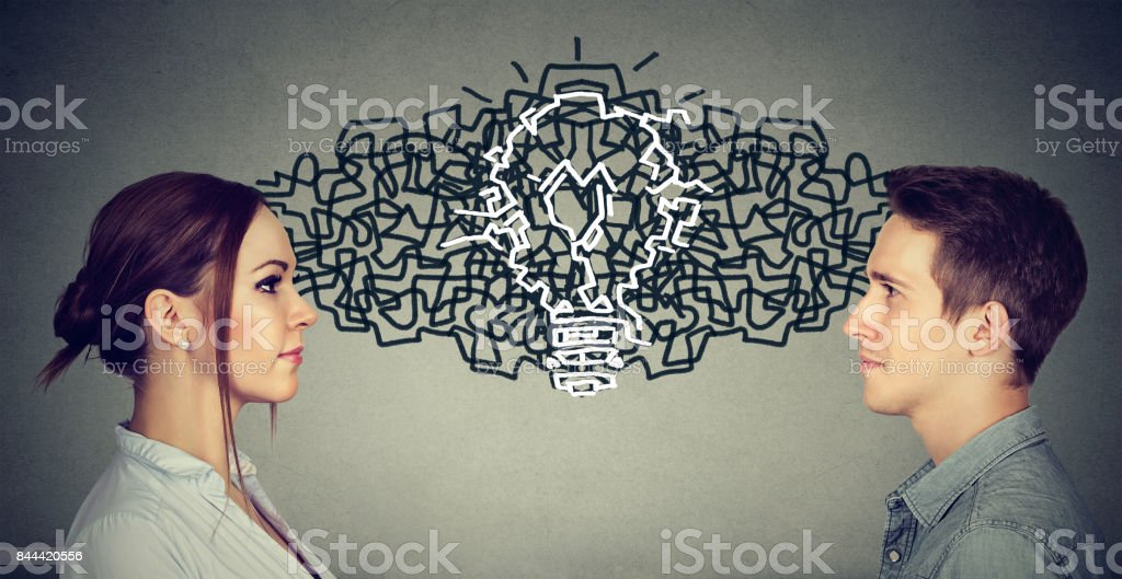 Young man and woman looking at each other exchanging their thoughts coming up together with an idea light bulb stock photo