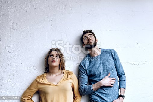 istock young man and woman looking up in the air 624712984