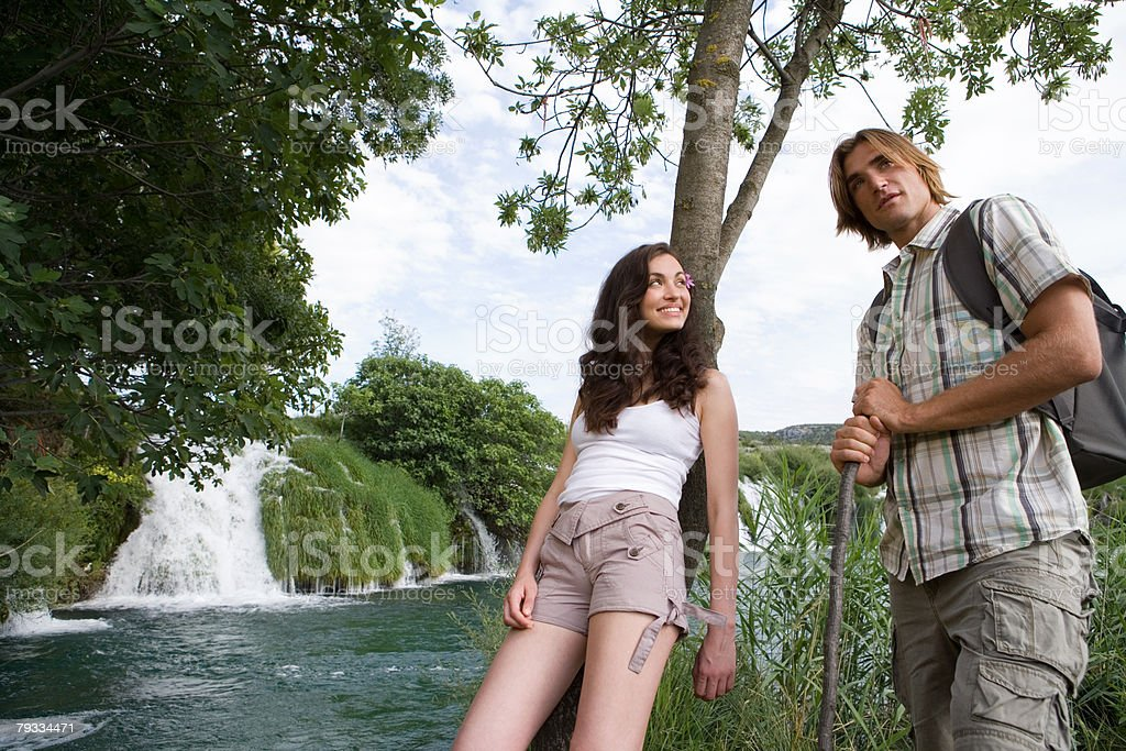Young man and woman near a waterfall 免版稅 stock photo