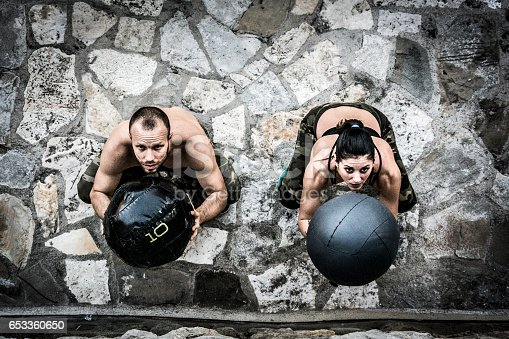 istock Young man and woman on cross training throwing medicine ball 653360650