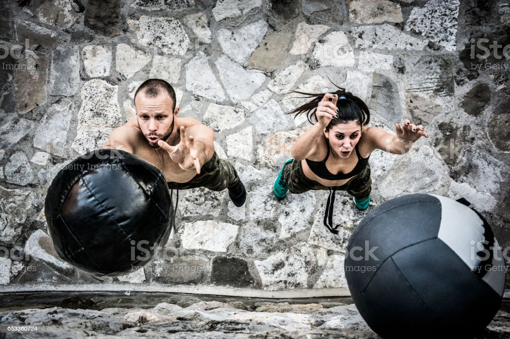 Young man and woman on cross training throwing medicine ball stock photo