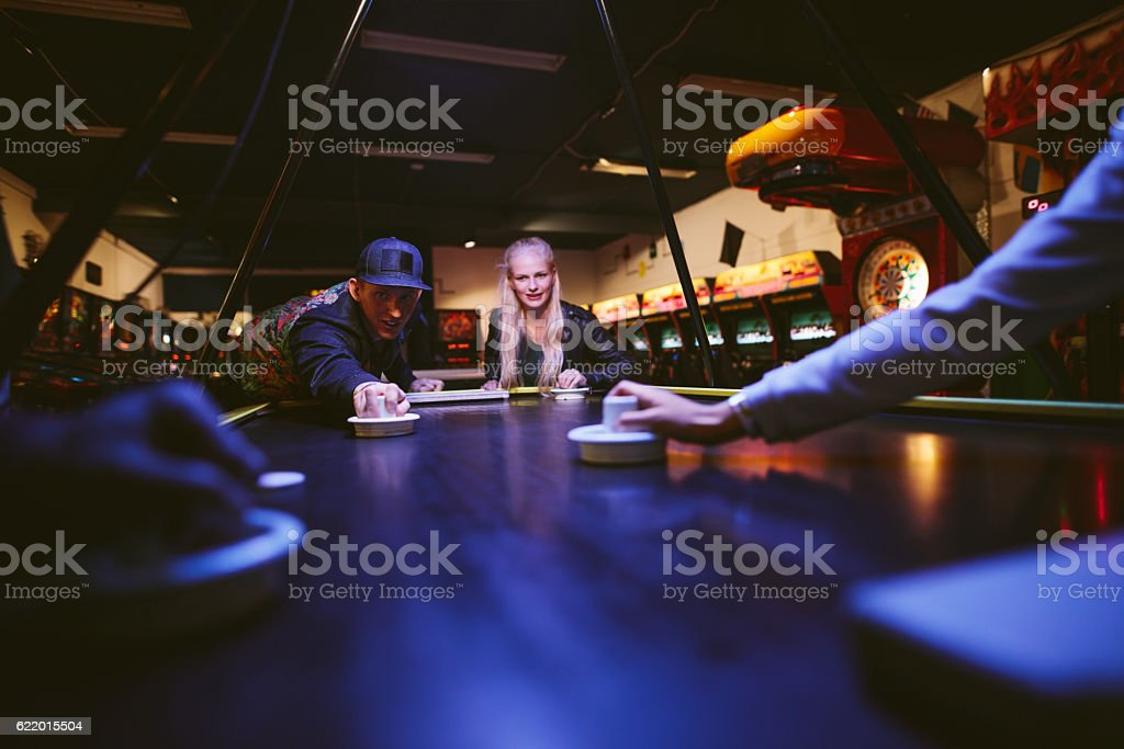 Young man and woman playing air hockey game - foto de acervo