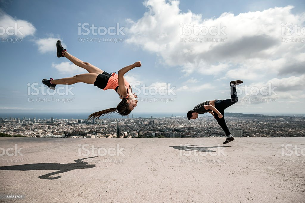 Young man and woman practicing parkour in the city stock photo