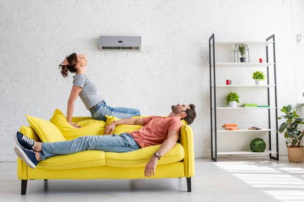 junge Mann und Frau ruht auf gelbem Sofa unter Klimaanlage zu Hause – Foto
