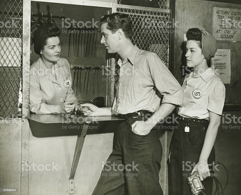 Young man and woman returning tools at tool room window, (B&W) stock photo