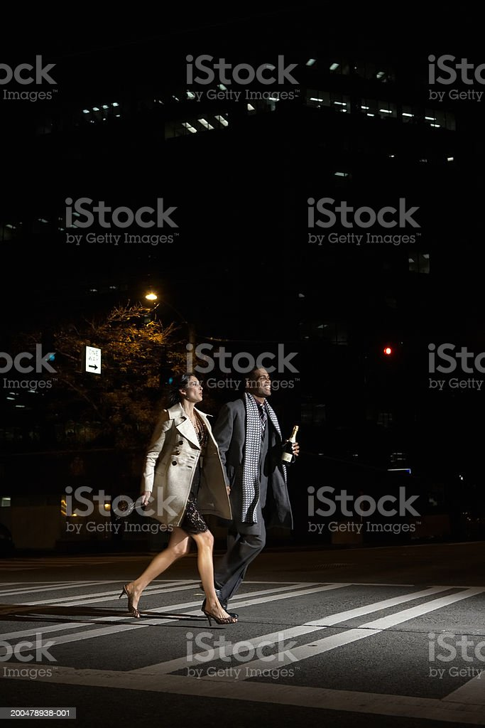Young man and woman running across street at night royalty-free stock photo