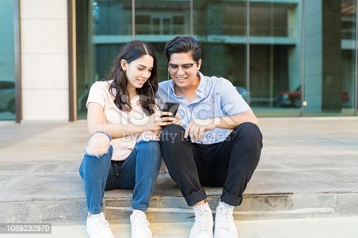 Full length of cute couple checking out mobile phone while listening music outside shopping center