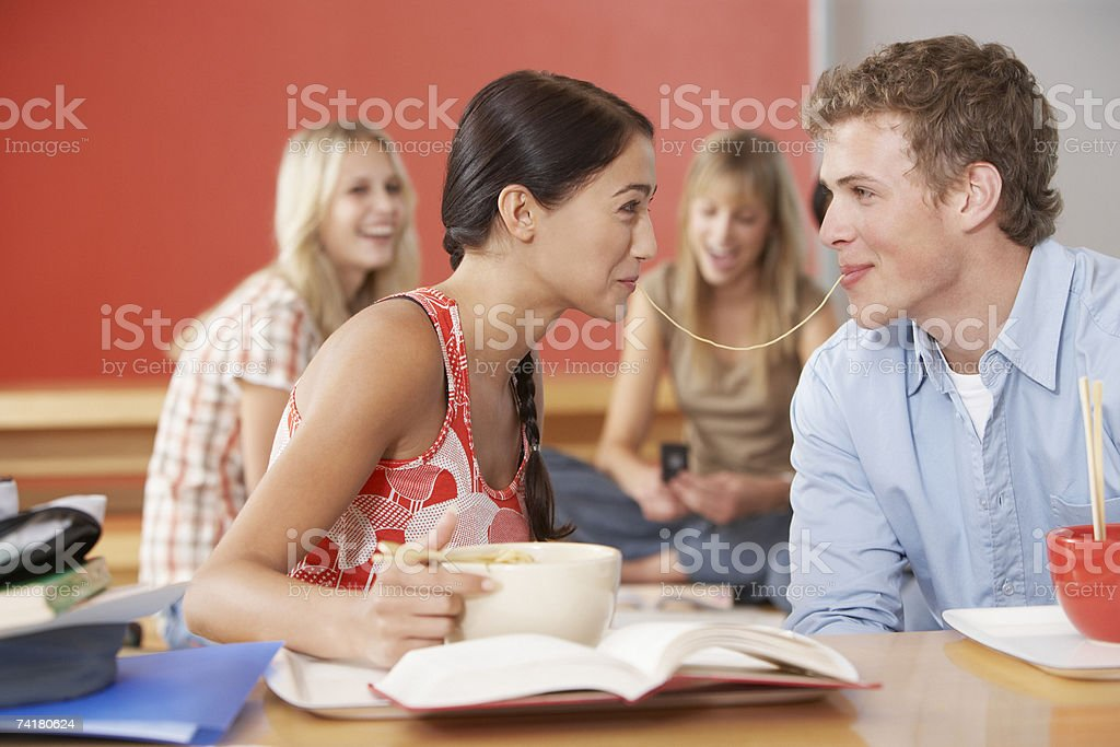 Jovem e mulher a partilha de noodle na Cantina foto de stock royalty-free