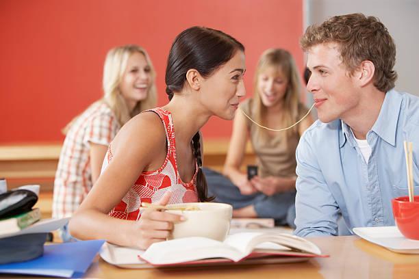 giovane uomo e donna nella caffetteria condivisione di pasta - compagni scuola foto e immagini stock