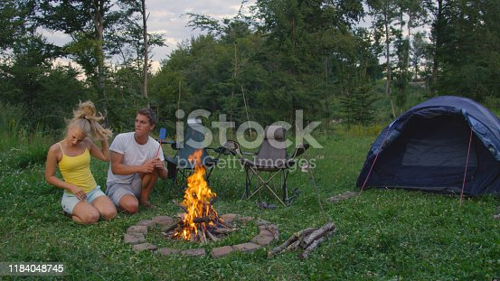 COPY SPACE: Young Caucasian man and woman sitting by the campfire get irritated by pesky bugs coming from the forest. Funny shot of couple waving their arms to repel annoying mosquitoes from campsite.