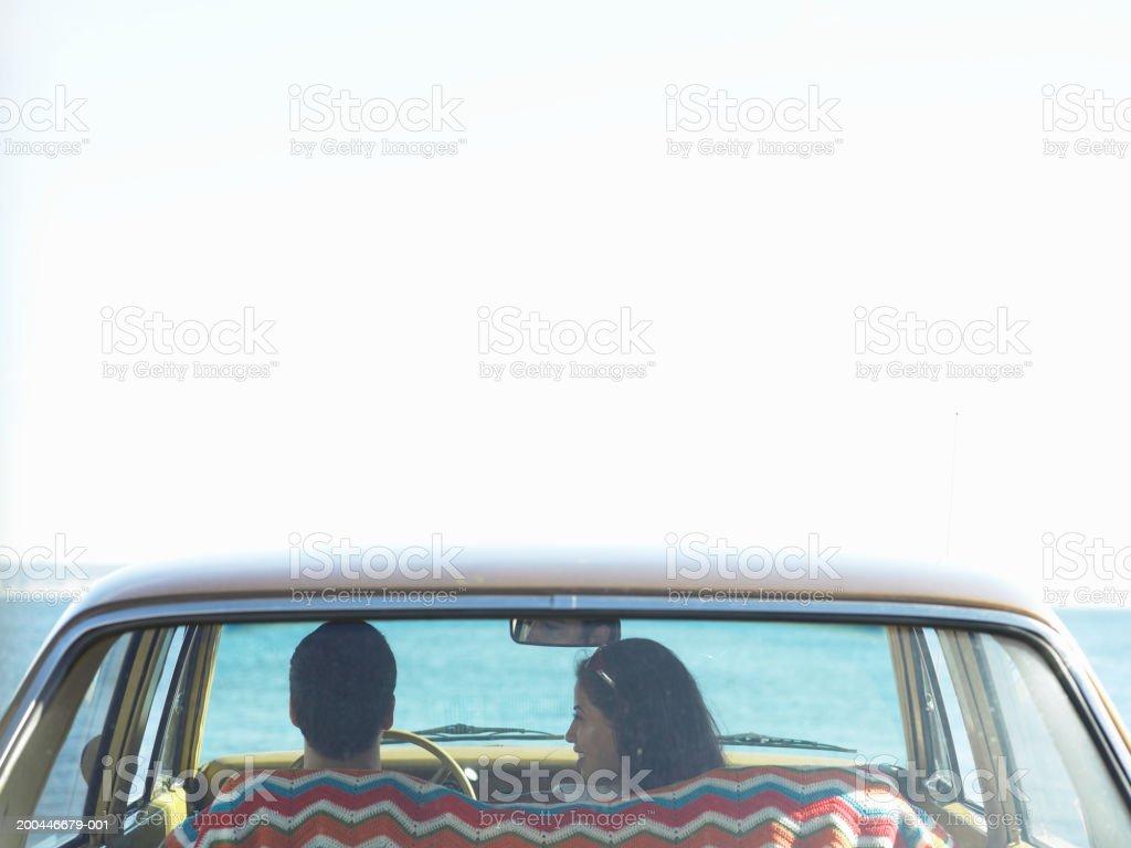 Junger Mann und Frau sitzt im Auto am Meer, hinten – Foto