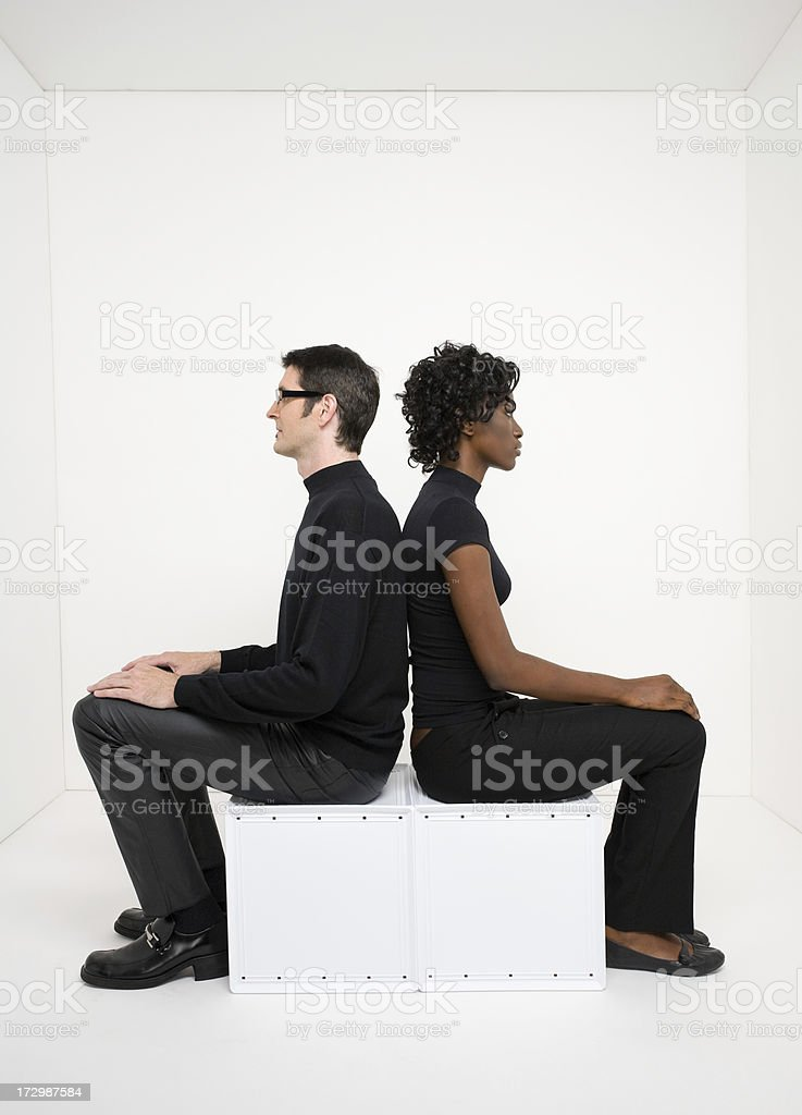 Young man and woman sitting in stark white room royalty-free stock photo