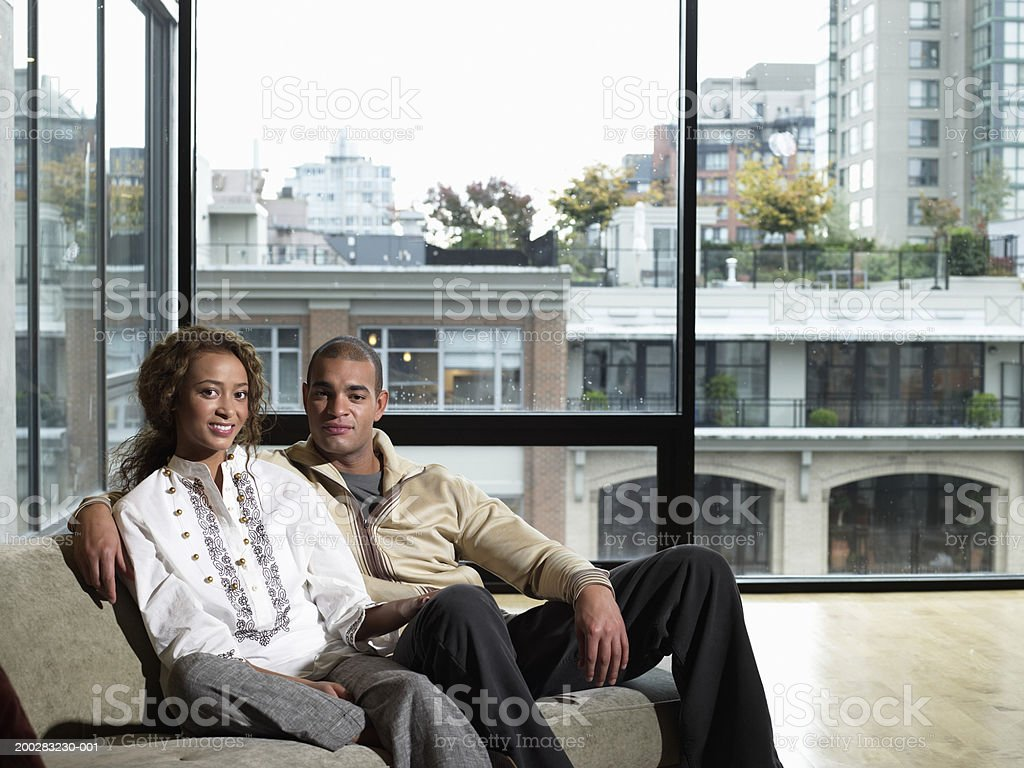 Young man and woman sitting on sofa, smiling, portrait royalty-free stock photo