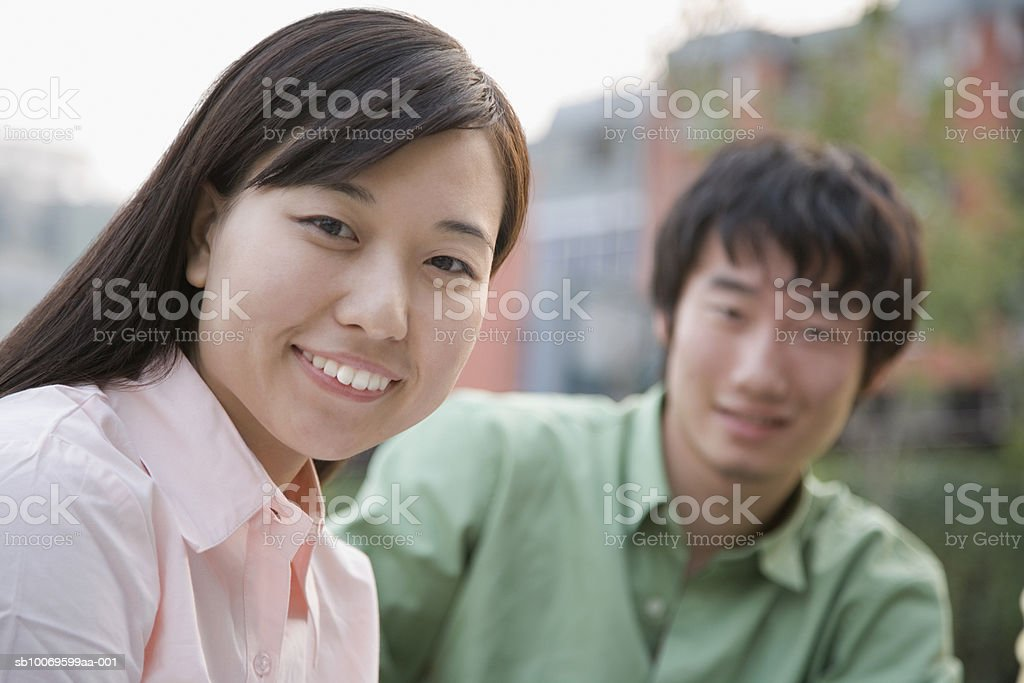 Young man and woman smiling, focus on woman in foreground, portrait royalty-free 스톡 사진