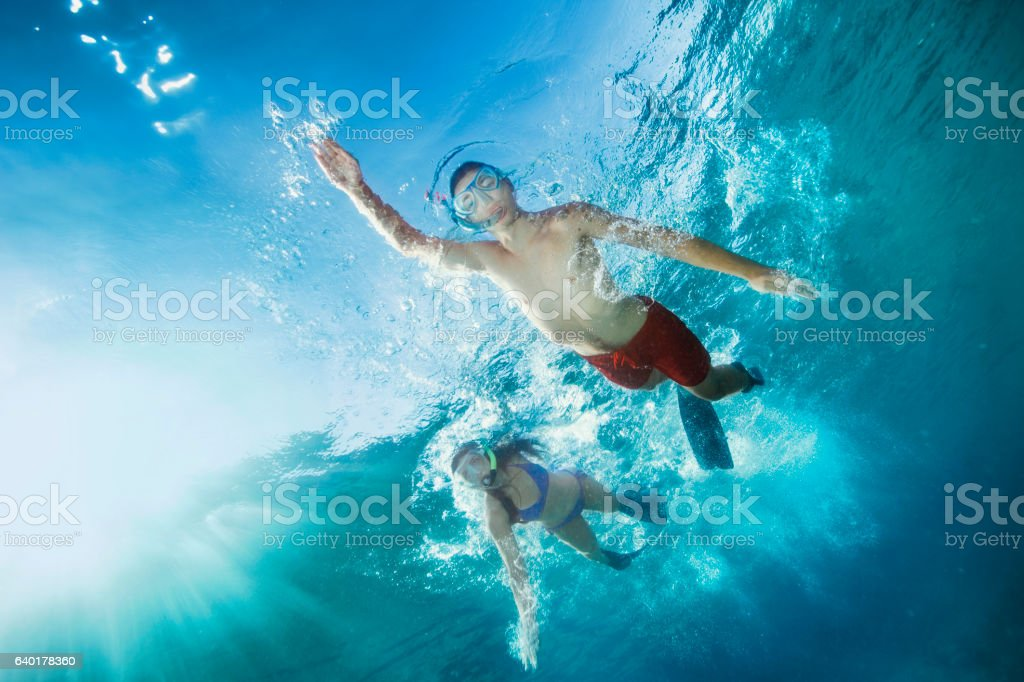Young man and woman snorkeling  Underwater diving adventure  Turquoise sea stock photo