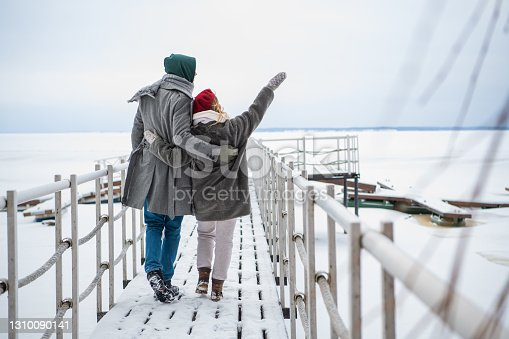 A young man and woman spend time together on a winter vacation, walking on a snow-covered pier on the river.