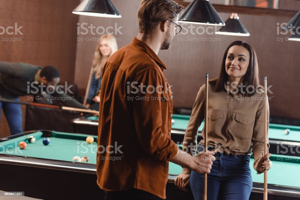 young man and woman standing beside pool table and looking at each other at bar with friends - Royalty-free Adult Stock Photo
