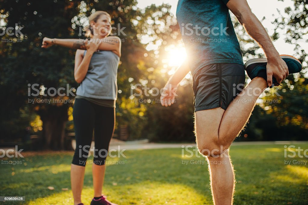Young man and woman stretching in the park stock photo