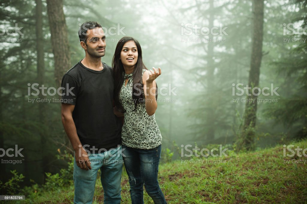 Young man and woman together in nature enjoying scenic beauty. stock photo