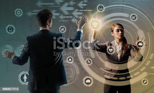 861122560 istock photo young man and woman using futuristic user interface, abstract image visual 696807010