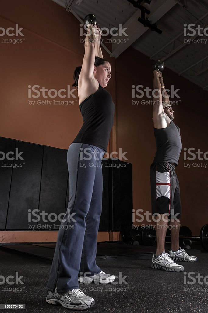 Young Man and Woman Using Kettle Bells royalty-free stock photo