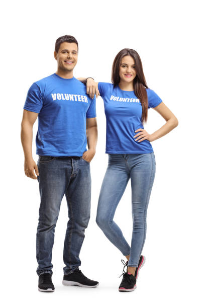 young man and woman volunteers in blue t-shirts posing - contributor stock pictures, royalty-free photos & images
