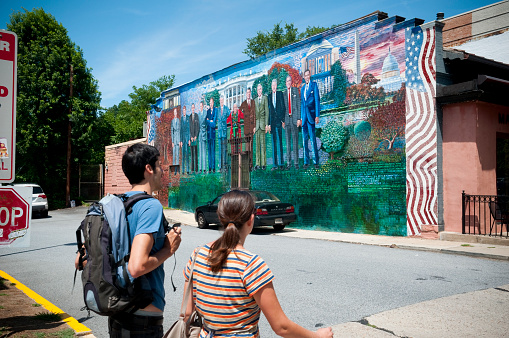 Washington DC, USA - June 16, 2012: A young man and woman walk past a mural of several U.S. Presidents (from Eisenhower to Obama), painted on the wall of Mama Ayesha's restaurant in the Adams Morgan area of Washington DC.