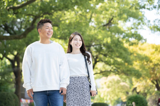Young man and woman walking friendly against a beautiful green background stock photo