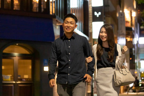 Young man and woman walking happily in the downtown area at night stock photo