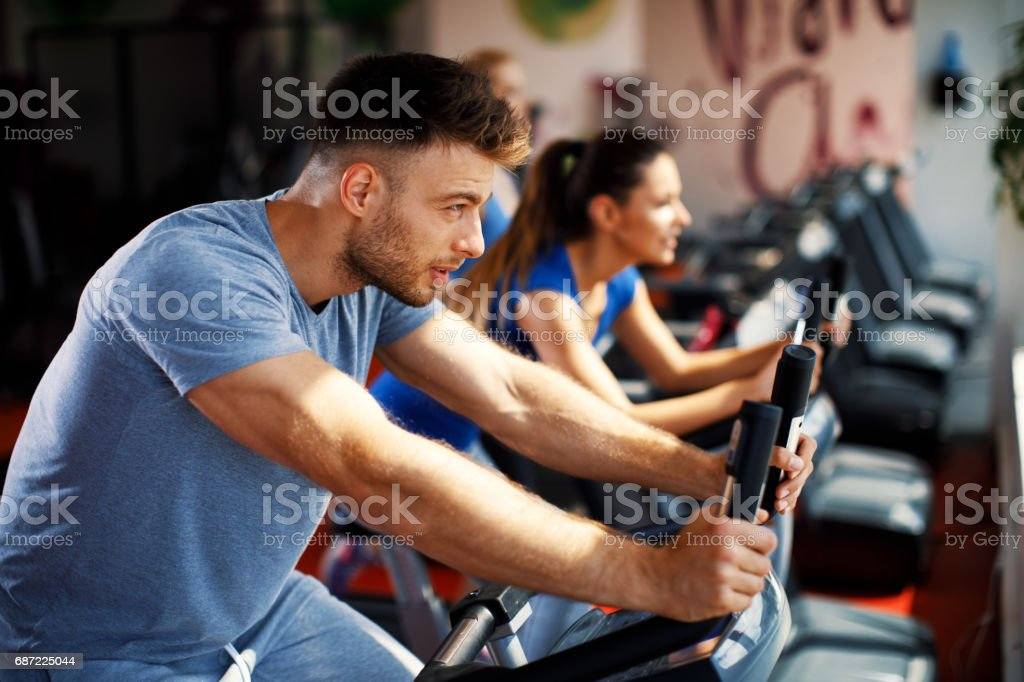 Young man and woman warming up on bikes in the gym stock photo