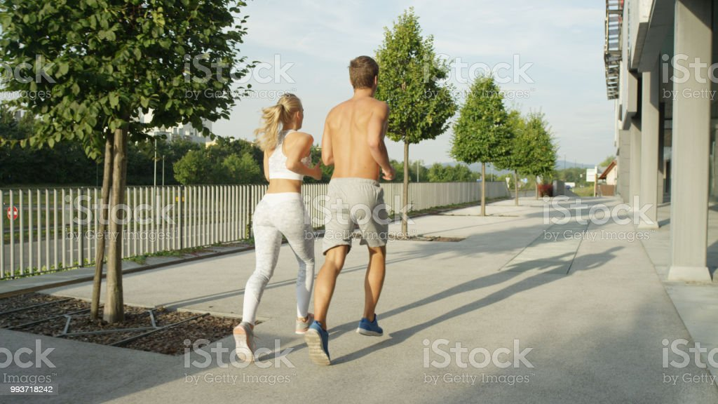 Unrecognizable young man and woman with athletic physiques working...