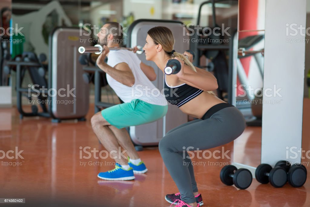 young man and woman with barbell flexing muscles and making shoulder press squat in gym stock photo
