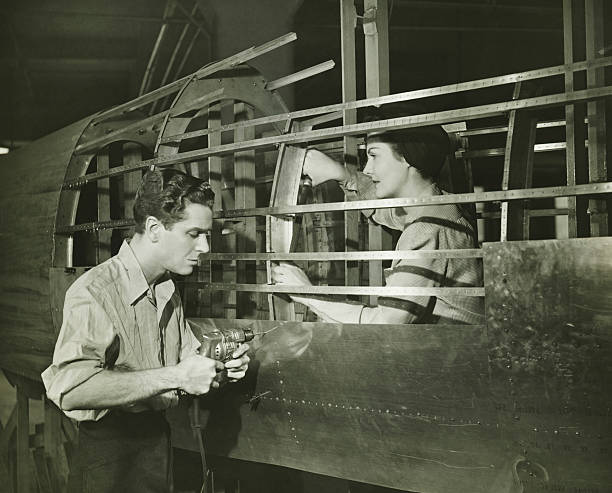 Young man and woman working in plane body in factory, (B&W) stock photo