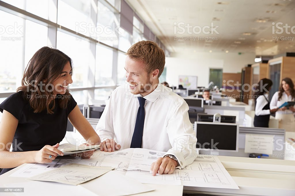 Young man and woman working together in architects office stock photo