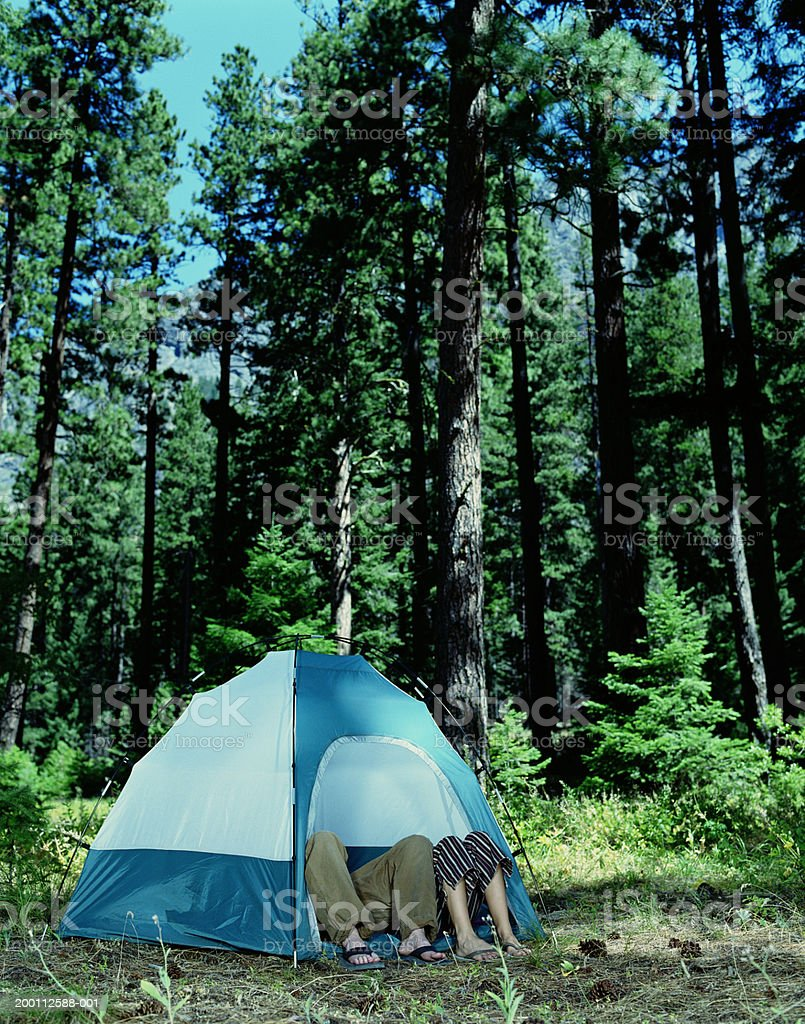 Young man and woman's legs sticking out of tent royalty-free stock photo
