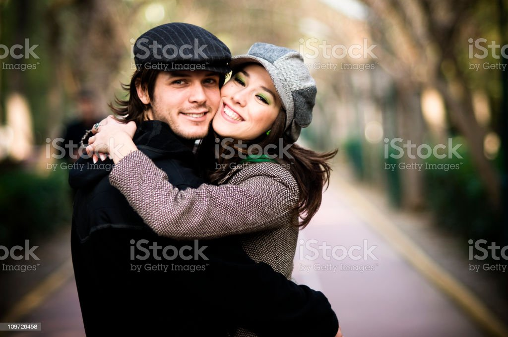A young man and women hugging each other affectionately stock photo