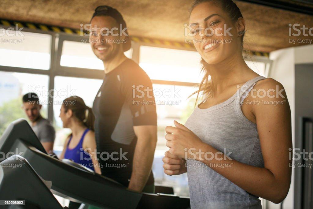 年輕的男人和女人在健身房鍛煉。朋友一起在健身房跑步機上。看著相機的女人。 免版稅 stock photo