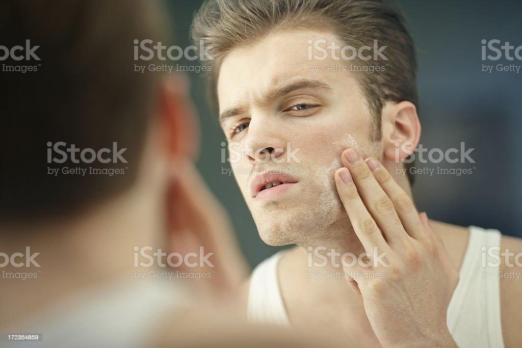 Hombre joven aplicar una crema facial front of the mirror foto de stock libre de derechos