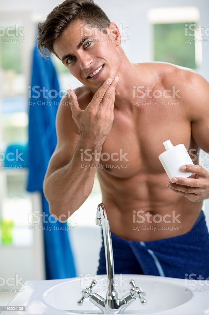 Young man applying after shave stock photo