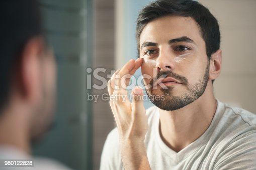 istock Young Man Applying Anti-aging Lotion fot Skin Care 980122828