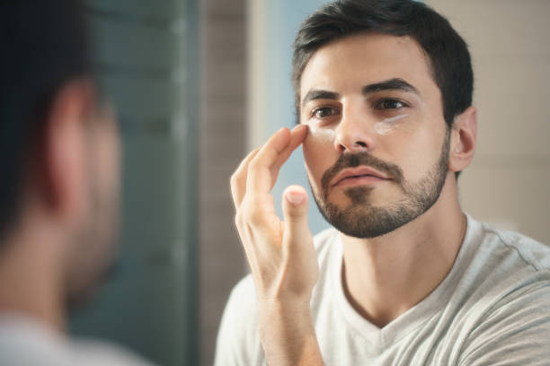 Young Man Applying Anti-aging Lotion fot Skin Care Young hispanic people and male beauty. Metrosexual man applying lotion for anti-aging treatment around eye antiaging stock pictures, royalty-free photos & images