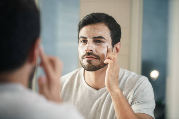 Young Man Applying Anti-aging Lotion fot Skin Care stock photo