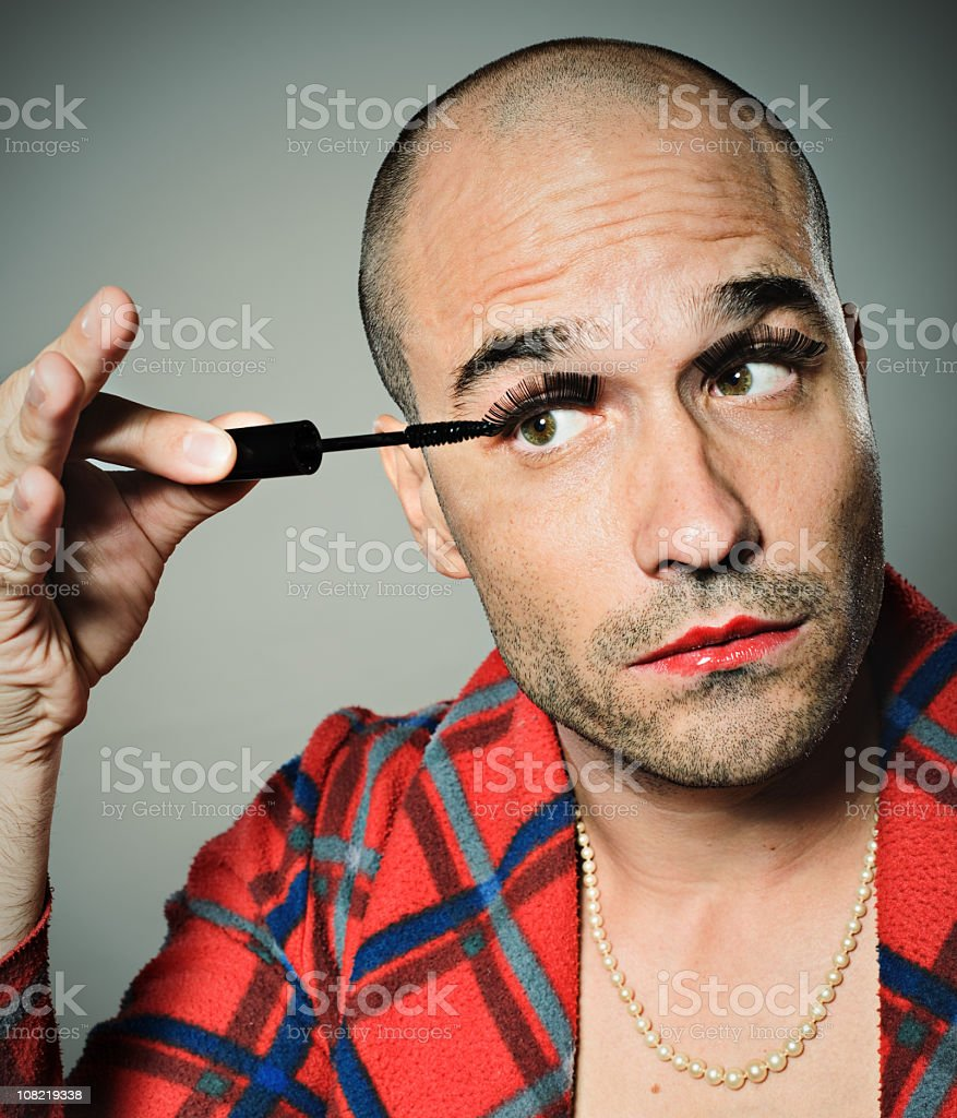 Young Man Applying False Eyelashes and Mascara stock photo