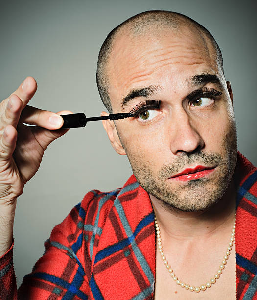 young man applying false eyelashes and mascara - transvestite stock photos and pictures