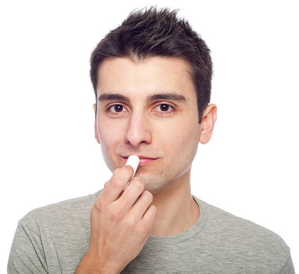 Young man applying lip balm stock photo
