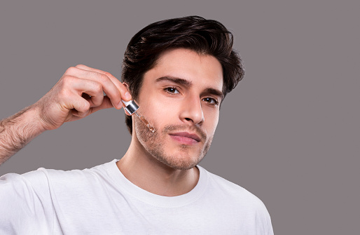 istock Young man applying organic essential serum on face 1164158686