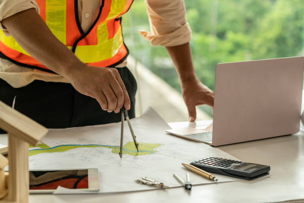 Young man architect or engineer working at desk with designer equipment to make interior design at workplace. Real estate business and civil engineering concept. stock photo