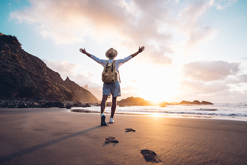 Young man arms outstretched by the sea at sunrise enjoying freedom and life, people travel wellbeing concept