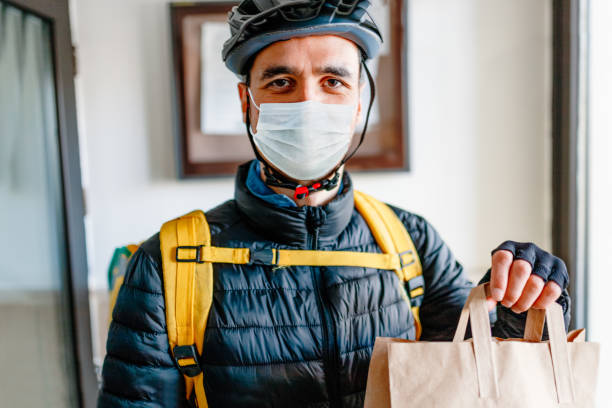 young man as a courier delivering  food - servizi essenziali foto e immagini stock