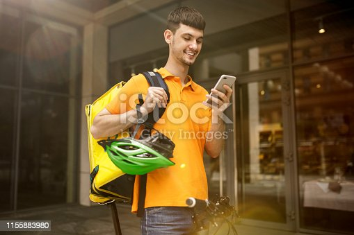 istock Young man as a courier delivering package using gadgets 1155883980